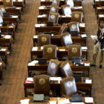 A member of the Sergeant at Arms, Jack Adams, places updated resolutions on the empty desks of House Representatives at the State Capitol on Sunday, May 26, 2013, in Austin, Texas. Members of the House of Representatives left the chamber to gather in their respective caucuses before returning to continue the 83rd Legislature.  (AP Photo/Austin American-Statesman, Rodolfo Gonzalez)
