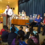 Houston Federation of Teachers President Zeph Capo addresses students and faculty to kick off a First Book distribution in Houston. Seated are AFT President Randi Weingarten and Houston ISD Superintendent Richard Carranza.