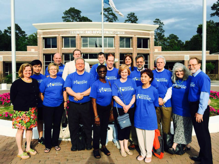 Group photo of A-F-T Lone Star College members in matching blue shirts standing outside of an administration building