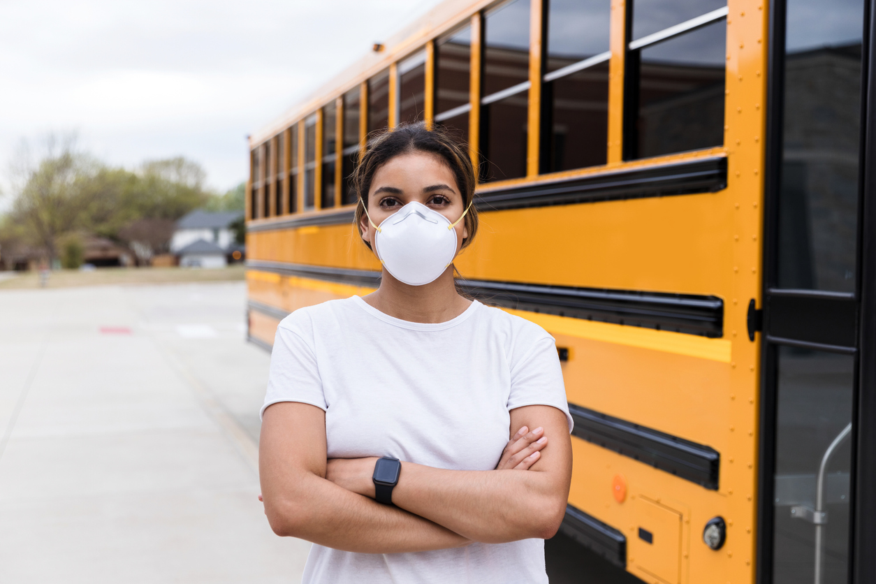Person with face mask stands with arms crossed next to school bus.