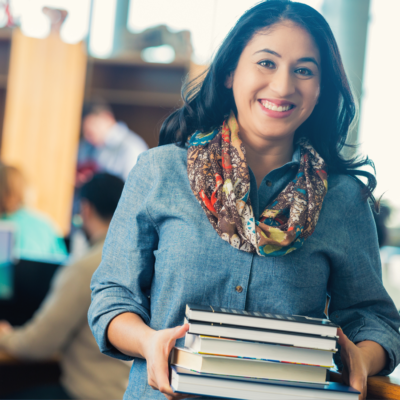 A teacher holding a stack of books.