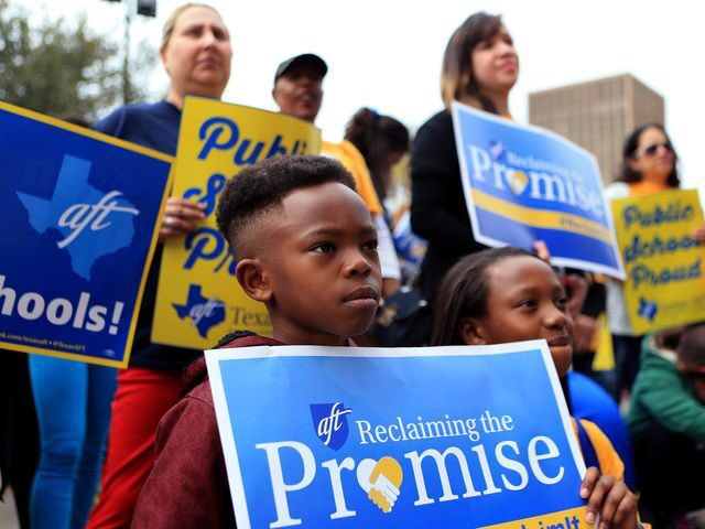 """Child stands in front of activists with sign that reads: """"AFT: Reclaiming the Promise."""""""
