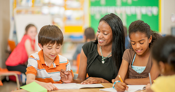 A teacher with two students working on assignments in a classroom.