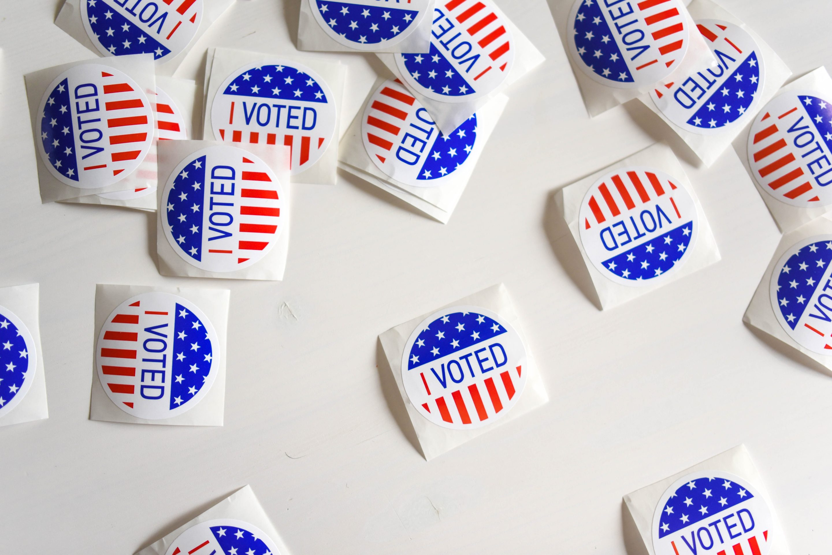 """I Voted"" stickers scattered on a white table."