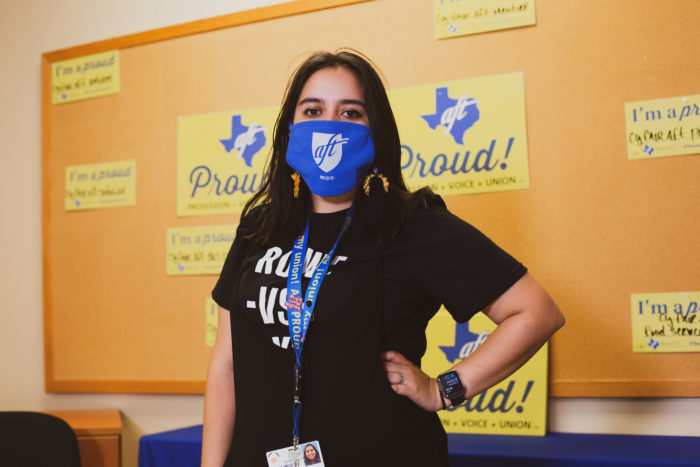 "Mariah Najmuddin poses with hand on hip and an A-F-T face mask in front of a corkboard with yellow ""Texas A-F-T Proud"" signs."