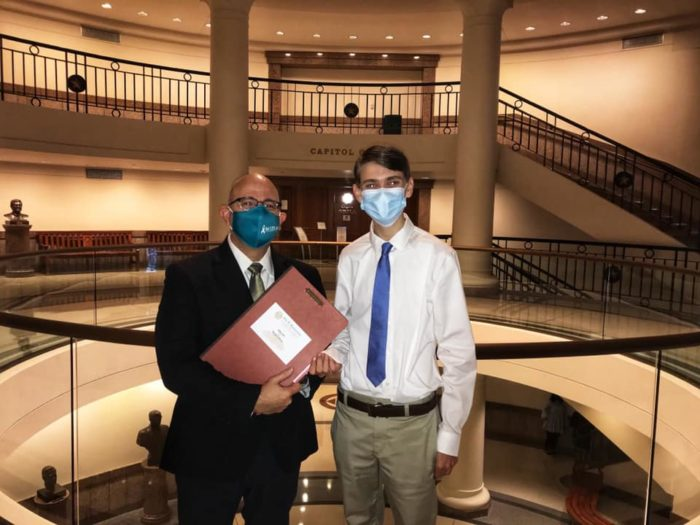 Representative Jon Rosenthal and Riley Schaudel pose together near the Capitol rotunda. They are both wearing face masks.