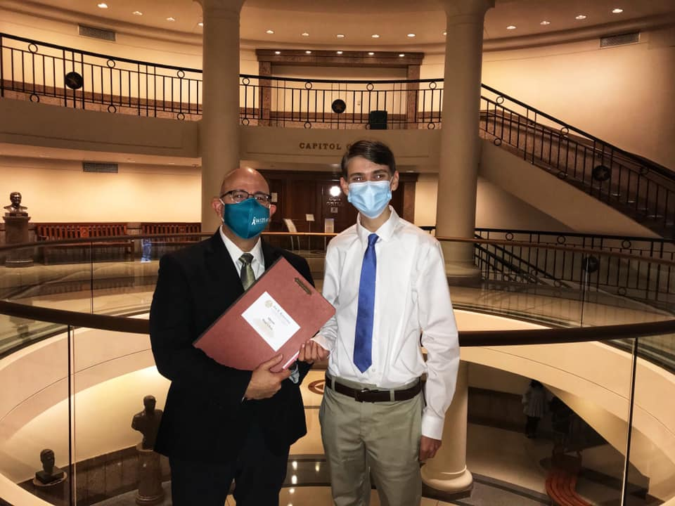 Representative Jon Rosenthal and Riley Schaudel pose together near the Texas Capitol rotunda. They are both wearing face masks.