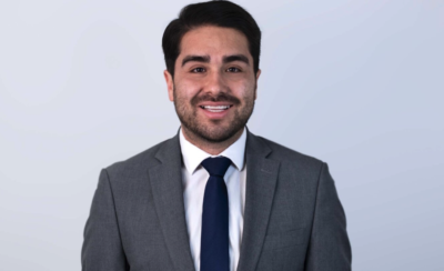 Photo of Joshua Acevedo, wearing a suit and smiling.