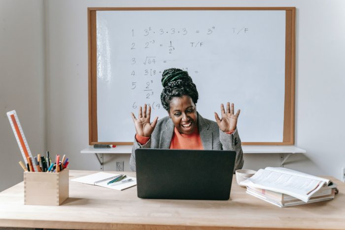 A teacher looks at their laptop while seated at a desk in a classroom. They are smiling and raising their hands.