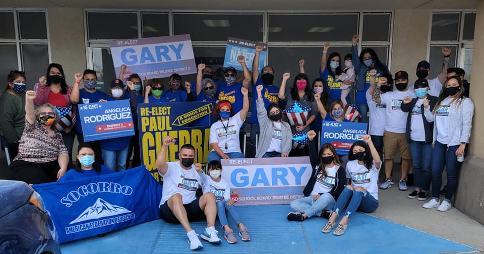 Socorro A-F-T members pose for a photo outside a building. All are wearing face masks and some are holding signs for endorsed school board candidates.
