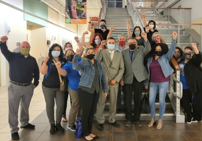 Group photo of Socorro school board members and Socorro A-F-T members and leaders. They are wearing face masks and raising their fists in solidarity.