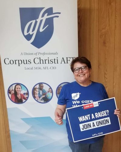 "Doctor Nancy Vera stands in front of a Corpus Christi A-F-T banner. She holds a sign that reads, ""Want a raise? Join a union."""